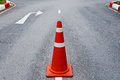 Orange traffic cone on asphalt road with white arrow to turn right ahead Royalty Free Stock Photos