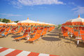 Orange umbrellas and chaise lounges on the beach of Rimini in It