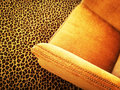 Orange velvet armchair on leopard carpet Royalty Free Stock Photo