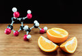 Orange and vitamin c structure model ascorbic acid on wood with black background Royalty Free Stock Image