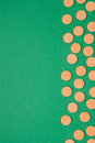 Orange vitamin pills on a green background Royalty Free Stock Photography