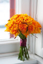 Orange wedding bouquet of roses on a windowsill by a window Stock Photography