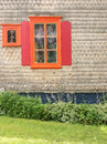 Orange window red shutters and wood siding an old shingle sided house with an Stock Photos