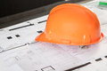 Orange worker helm a is laying on a architecture floor plan Royalty Free Stock Photo