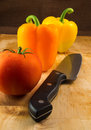 Orange and yellow peppers ripe tomato and knife a rip on a wooden cutting block with a slicing Royalty Free Stock Image