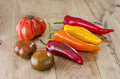 Orange yellow and red bell pepper and costoluto genovese tomato on wood background Royalty Free Stock Photography