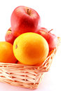 Oranges and apples in a basket close up view with white background Stock Photo