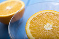 Oranges on a blue wooden table and glass bowl Stock Photos