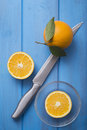 Oranges on a blue wooden table knife and glass bowl Royalty Free Stock Photo