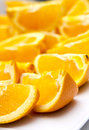 Oranges cut in quarters orange on a white plate Stock Image