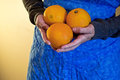 Oranges female hands holding over a blue apron Stock Images