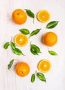 Oranges fruits composition with green leaves and slice on white wooden background top view Stock Photography
