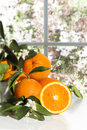 Oranges near kitchen window fresh on white surface with in background Royalty Free Stock Image
