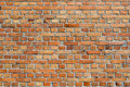 Orangey red brick wall background texture and pattern with alternating rows of long and short bricks Royalty Free Stock Images