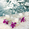Orchids and candles by pool. Royalty Free Stock Images