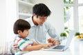 Ordenador portátil asiático del uso de helping son to del padre en casa Imagen de archivo libre de regalías