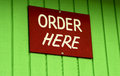 Order here sign on green wall Stock Photo