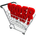 Order now words shopping cart purchase e commerce buy store the in a basket to symbolize ecommerce and browsing or buying from an Stock Images