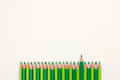 Ordered group of bright green pencils on white background with one pen standing out Royalty Free Stock Photo