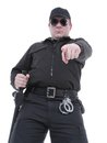 Ordering policeman wearing black uniform and glasses pointing in manner Stock Photo