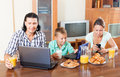 Ordinary couple with teenager son happy using devices during breakfast at home Stock Photo