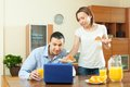 Ordinary couple using laptop during breakfast man laptot wife serves morning her husband men at home Royalty Free Stock Image