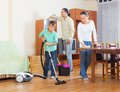 Ordinary family doing housework together of three in home Stock Images