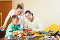 Ordinary family of three doing something with the working tools Royalty Free Stock Photo