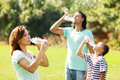Ordinary family of three drinking from bottles plastic in summer park Stock Photo