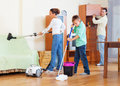 Ordinary family of three with teenager doing housework cleaning equipment in living room Stock Photography