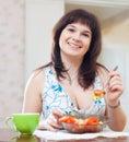 Ordinary girl eats veggie salad on sofa positive Stock Photo