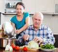 Ordinary senior couple cooking with vegetables in home kitchen Stock Photos