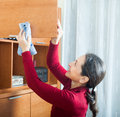 Ordinary woman cleaning wooden furniture with rag at home Royalty Free Stock Images