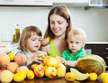 Ordinary woman with daughters eating fruits women two melon and peaches Royalty Free Stock Image