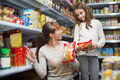 Ordinary woman with girl standing near shelves Royalty Free Stock Photo