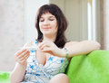 Ordinary woman looks by thermometer sick at home Stock Photos
