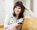 Ordinary woman sends sms by mobile on sofa in home Royalty Free Stock Photography