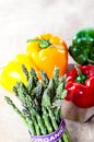 Organic asparagus on blurred background with copy space selective focus and colored peppers top Royalty Free Stock Photo