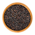 Organic black rice in wooden bowl over white Royalty Free Stock Photo