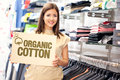 Organic cotton clothes a beautiful shop assistant holding the sign Stock Images
