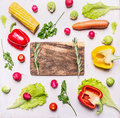 Organic farm vegetables lined frame with a chopping board in the middle on wooden rustic background top view close up Royalty Free Stock Photo