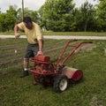 Organic farmer starting a old garden tiller older Stock Photography