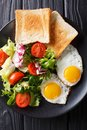Organic food breakfast: fried eggs with fresh vegetable salad an Royalty Free Stock Photo