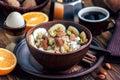 Organic oatmeal porridge in dark ceramic bowl with bananas, honey, almonds, pistachio, coconut chips, orange, cinnamon and raisins