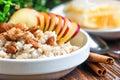 Organic oatmeal porridge in white ceramic bowl with apple, almond, honey and cinnamon. Healthy breakfast Royalty Free Stock Photo