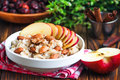 Organic oatmeal porridge in white ceramic bowl with apple, almond, honey and cinnamon. Healthy breakfast Royalty Free Stock Photo