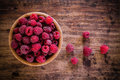 Organic raspberries in a bowl on wooden background bright fresh old Royalty Free Stock Photo