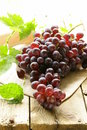 Organic ripe black grapes on a wooden table Stock Photo