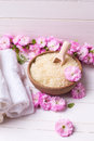 Organic sea salt in bowl with towels and pink flowers Royalty Free Stock Photo