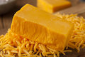 Organic sharp cheddar cheese on a cutting board Stock Images